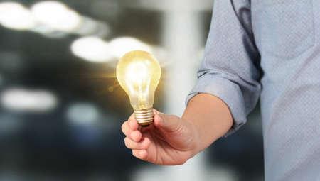 Hand holding illuminated light bulb, idea, innovation and inspiration concept 写真素材