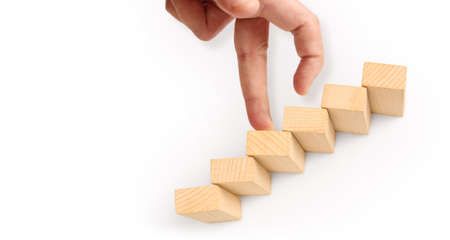 Hand liken person stepping up a toy staircase wood Stock Photo - 129810582