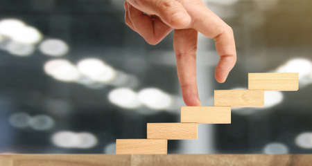 Hand liken person stepping up a toy staircase wood Stock Photo