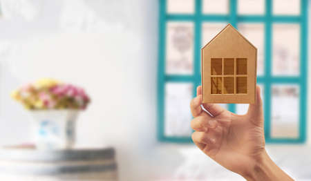 Wooden toy house. Mortgage property home concept. Buying house for family. model in hand