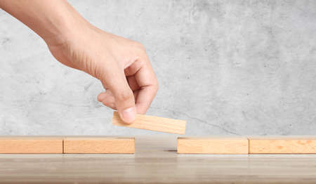 Hand liken person stepping up wood block stacking as step stair, business idea Фото со стока