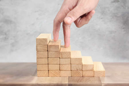Hand liken person stepping up a toy staircase wood Фото со стока