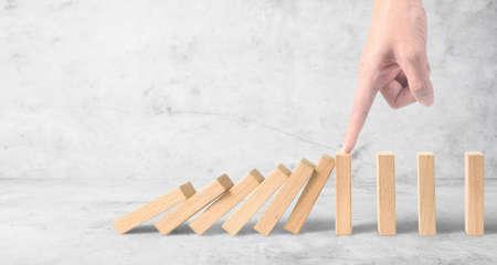 Mano che ferma l'effetto Domino fermato da idee imprenditoriali uniche