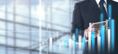 Hand holding smartphone device and touching screen. Stock exchange market concept. businessman trader looking on with graphs analysis candle Zdjęcie Seryjne