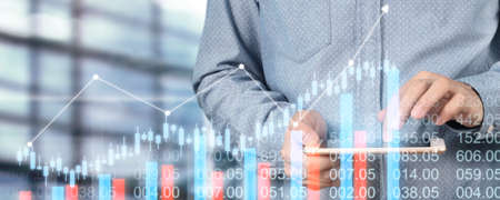 Hand holding smartphone device and touching screen. Stock exchange market concept. businessman trader looking on with graphs analysis candle