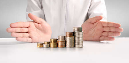 Coins stacked on each other in different positions,Man hand in business casual money Фото со стока