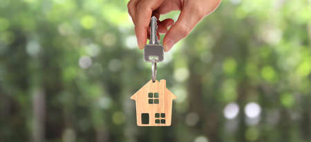 Real estate agent handing over house keys in a hand