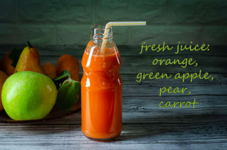 Fresh juice from orange green apple with pears and carrots in a bottle with a straw front view on a wooden background with text Imagens