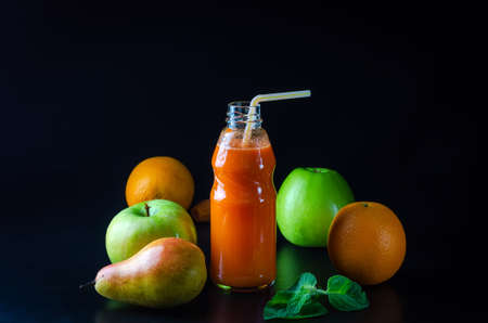 fresh juice from orange green apple with pears and carrots in a bottle with a straw front view on a black background