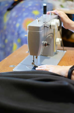 working with a black cloth on a Soviet sewing machine with black threads Banco de Imagens - 124978645