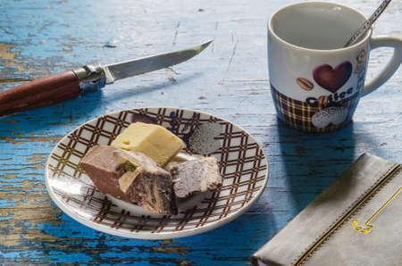 morning coffee with chocolate halva on a wooden old background with a knife and notepad