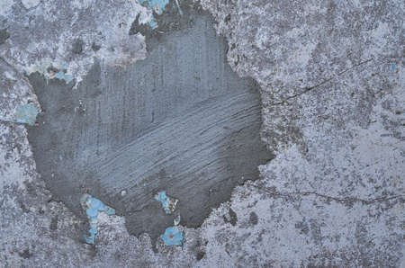 grunge concrete wall with broken blue paint closeup. Texture of old lime and concrete
