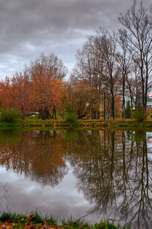Trees with yellow and red leaves on the banks of a pond in an autumn park are reflected in the water. October