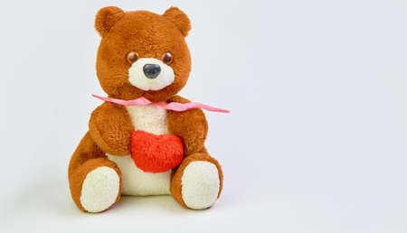 Teddy bear with a red heart in hands on a light background with place for text. Imagens