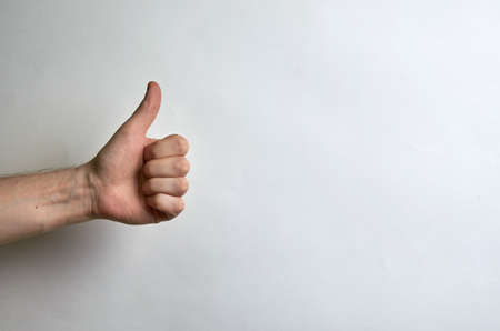 Thumb male left hand on a white background with place for text. Like, approval, cool, compliment Banco de Imagens