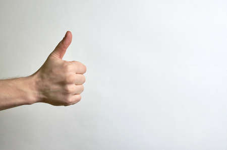 Thumb male right hand on a white background with place for text. Like, approval, classy, compliment male left hand on a white background with place for text. How, approval, cool, compliment Banco de Imagens
