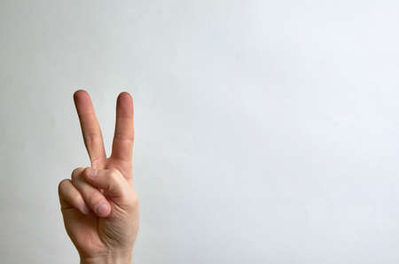 Two fingers up on the hand, peace symbol on a white background with a sweep for text. Copy space