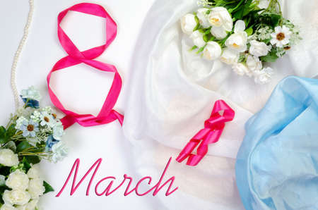 International Womens Day, March 8th. Number eight from a red satin ribbon on an airy satin fabric background with a bouquet of flowers and pink pearls, top view with the inscription March 8