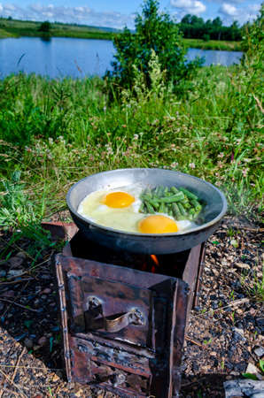 Scrambled eggs are fried on a homemade stove in a frying pan over an open fire on the lake.