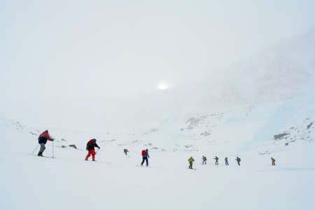 Skiers ride in the snow in the mountains of Baikal