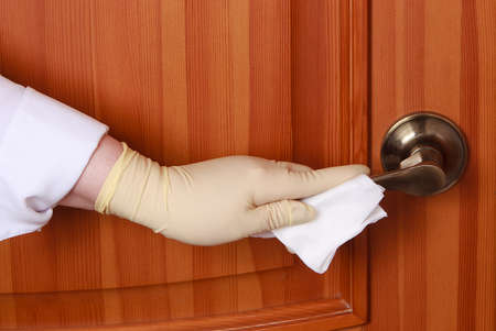 concept of disinfecting surfaces from bacteria or viruses sill-life, hand with glove cleaning door knob with disinfectant wet wipe