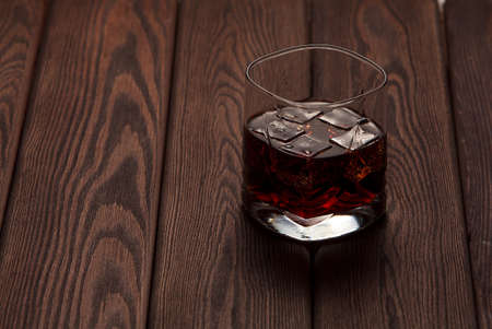 whiskey in a glass with ice in a dark wooden background