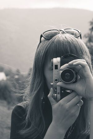old photograph: Outdoors portrait of a pretty young tourist taking photographs with vintage retro camera Stock Photo