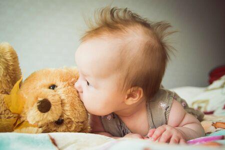 Bebé juega con un osito de peluche Foto de archivo
