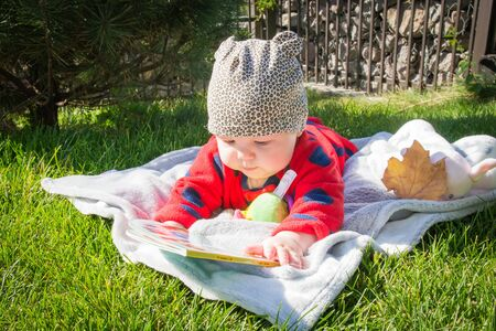 Beautiful little baby is reading a book on green grass