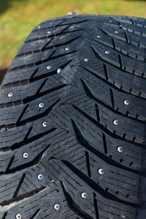 old tires, car tire with spikes. grass background.