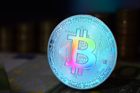 The rainbow physical bitcoin coin is BTC, preferably color blue. The concept of cryptocurrency.