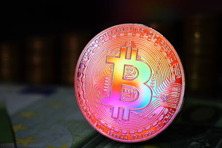 The rainbow physical bitcoin coin is BTC, preferably red and yellow color. The concept of cryptocurrency. Stockfoto