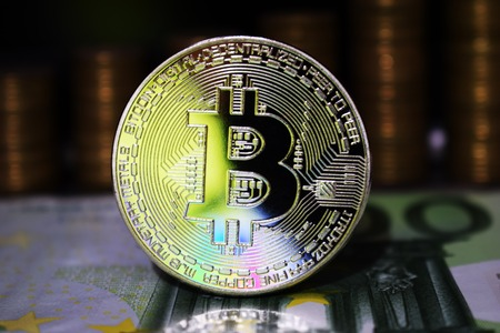 Beautiful Bitcoin BTC on the background of euro banknote and gold coins. The concept of cryptocurrency.