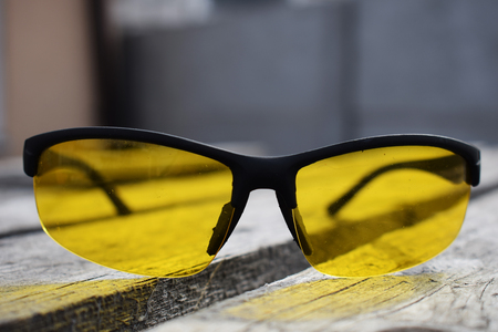Yellow glasses on a wooden background. Glasses lie. Black orange glasses . Imagens