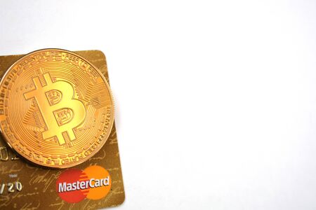 Bitcoin golden coin with MasterCard credit cards. White background. Editorial