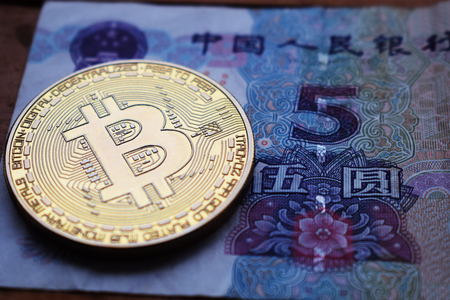 Bitcoin Gold Coin on Chinese Yuan banknote. Close up. 스톡 콘텐츠
