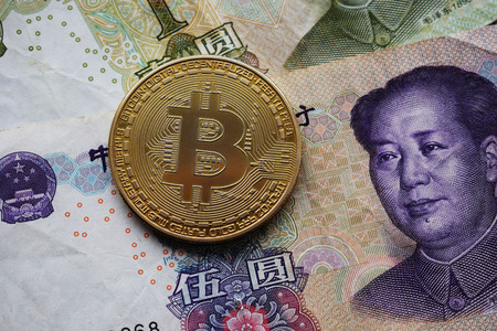 Golden Bitcoin Coin on Chinese Yuan banknote. Close-up. Stock Photo