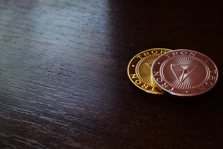 Tron coins on wooden background. Digital money. Free text space.