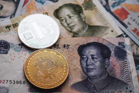 Bitcoin BTC and Litecoin LTC Coins on Chinese Yuan and US dollar. Close-up.