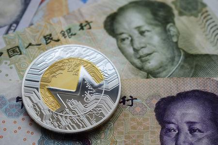 Monero XMR Coins on Chinese Yuan banknotes. Close-up.