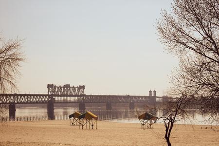Spring sunny warm day, the beach, the river and the view of the bunk bridge, Kremenchug. Zdjęcie Seryjne