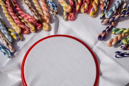 The embroidery hoop with canvas and colored sewing threads. 스톡 콘텐츠