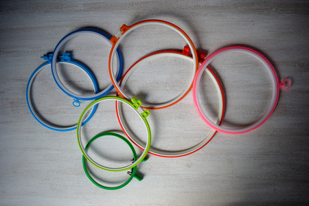 Multicolored embroidery hoops for creative art on a light background. View from above.