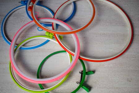 Multicolored embroidery hoops for creative art on a light background.
