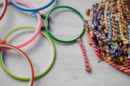 Multicolored embroidery hoops for creative art and threads of floss braided threads for embroidery on a light background.