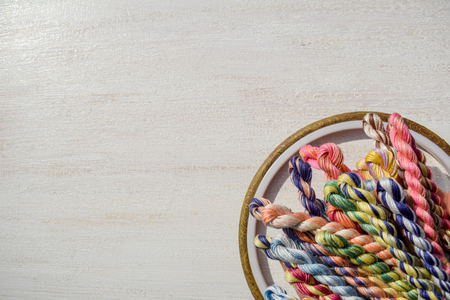 Embroidery hoops for creative art and braided floss threads for embroidery on a light background. Free text space. Creative concept.