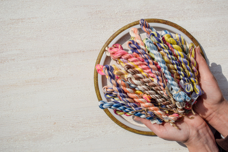 Braided threads for embroidery in female hands. Stock Photo