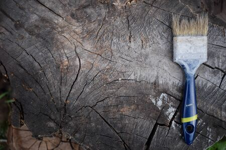 Brush on a wooden background. Painting wooden surface. Old brush. Gray paint.