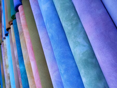 Rolls of colorful fabrics. Dyed fabric for sewing. Cross stitch fabric. Stock Photo