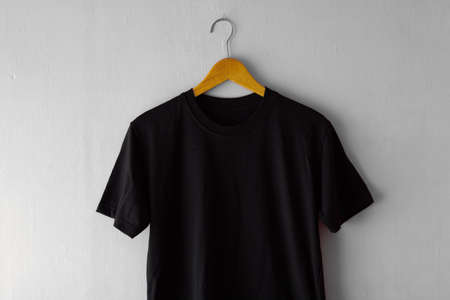 Blank black t-shirt on wood hanger with grey grunge wall background. Ready for your mock up design or presentation your design project.